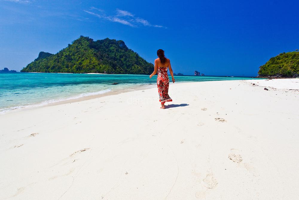 Woman walks along white sand beaches of Chicken Island (koh gai), Krabi, Thailand