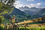 Mountain bikers push their bicycles up the Panoramaweg/Panorama Trail. Views of the Geisler/Odle Group and a church in St. Magdalena (Santa Maddalena) village are iconic of the Dolomites mountains. See the valley and municipality of Funes (Villnöss) in Trentino-Alto Adige/Südtirol (South Tyrol), Italy. Enjoy great hiking here in the vast Nature Park of Parco Naturale Puez-Odle (German: Naturpark Puez-Geisler; Ladin: Parch Natural Pöz-Odles). The Dolomites are part of the Southern Limestone Alps, Europe. UNESCO honored the Dolomites as a natural World Heritage Site in 2009.