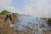 Man attempts to extinguish yet another fire caused by Palestinian Kite bombs that were flown from Gaza with a lit petrol soaked cloth, to set fires to Israeli fields and crops. Photographed on July 13, 2018 on the Israel Palestine (Gaza) Border
