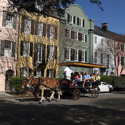 A carriage tour passing a portion of Rainbow Row, private residences painted eye-catching colors by their owners, Charleston, SC, USA