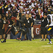 10 September 2016: The San Diego State Aztecs football team hosts Cal in their second game of the season. San Diego State running back Donnel Pumphrey (19) looks back at a defender as he scores on a 57 yard rushing touchdown. The Aztecs beat Cal 45-40 to keep their win streak at 12 games going back to last season and improve their record to 2-0.