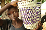 Southern Africa. Mozambique. .Young boy selling baskets to passing passengers in taxis..DVD0014