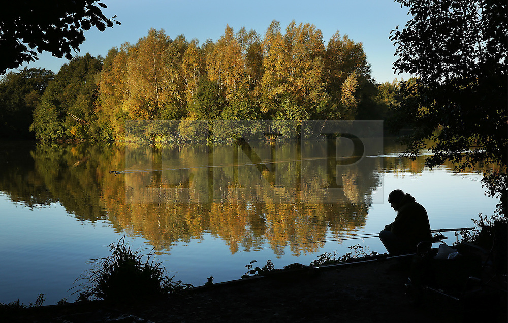 © Licensed to London News Pictures. 08/10/2015. Godalming, UK. A fisherman sits on the banks of Broadwater Lake as early morning sunshine illuminates the trees.  Photo credit: Peter Macdiarmid/LNP