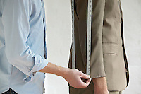 Tailor measuring jacket sleeve on man side view close up mid section