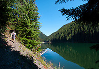 The mountains are reflected in the clear alpine lake of Strike Lake, part of the Lightning Lakes chain in Manning Park, BC as a hiker walks the trail.