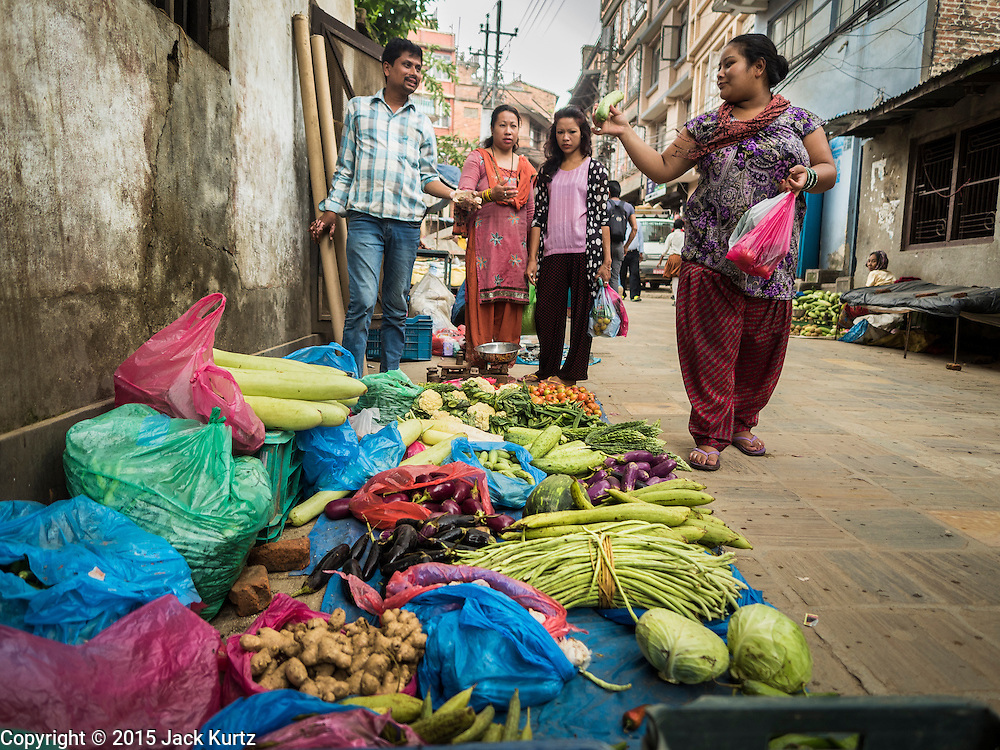06 AUGUST 2015 - KATHMANDU, NEPAL:  People buy fruits and vegetables at a street stand in Kathmandu.     PHOTO BY JACK KURTZ