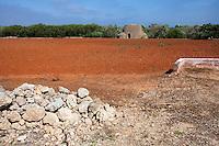 """Campo di terra rossa, tipica del Salento, appena arato. Sulla sfondo  un """"Caseddhu"""", tipica struttura delle campagne salentine che serviva in origine come rifugio temporaneo per i contadini."""