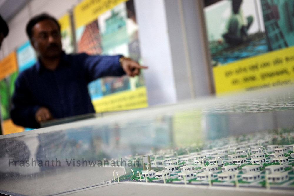 An employee points out to the proposed model town for diplaced villagers at the POSCO Kujanga office in Orissa, India, on Thursday July 1, 2010. Photographer: Prashanth Vishwanathan/Bloomberg News