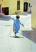 AFRICA, MOROCCO, TANGIER:  Young boy in traditional dress runs through the streets of the kasbah toward his mother.