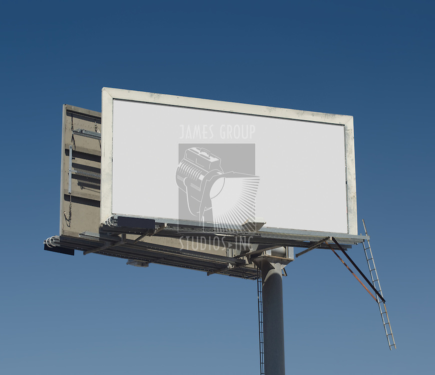 Blank freestanding billboard against a dark blue sky with clipping path for ad area