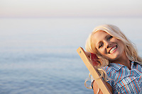 Young woman sitting on deckchair on beach close up portrait