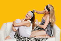 Young woman combing friend's hair while sitting on sofa over yellow background