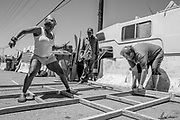 From left: Mona plays hopscotch as Oscar and Pete finish the wooden frame outside their camp at Wood Street and 26th Street on Thursday, June 15, 2017, in Oakland, Calif. The frame will be used to hold a cover for shade.
