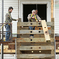 Adam Robison | BUY AT PHOTOS.DJOURNAL.COM<br /> Tim Denton, a employee for Lynn Bryan Construction, tosses a beam from the support cribbage, as he and Evan Atkins work to remove the old support on the veranda on the Spain House Wednesday afternoon. Steal beams were set in place earlier this week for permanent support.