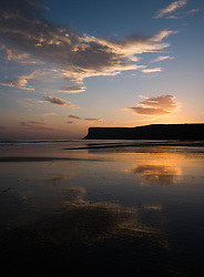 © Licensed to London News Pictures. <br /> 09/10/2014. <br /> <br /> Saltburn, United Kingdom<br /> <br /> Clouds are reflected in the wet sand as dawn breaks over Huntcliff in Saltburn by the Sea in Cleveland.<br /> <br /> Photo credit : Ian Forsyth/LNP