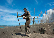 Man Digging To Find Megapode Birds Eggs In Tavurvur Volcano Sands, Rabaul, New Britain Island, Papua New Guinea. The volcano is also a good opportunity for locals to gain revenue. The Megapode birds live and nest at the base of Mount Tavurvur. They dig holes into the ash and bury their eggs 2 meters down until they reach the ground underneath, where the temperature is perfect. The Megapode egg serves as a primary source of food and income in Rabaul. Each day, men travel to the nesting grounds to gather the eggs.