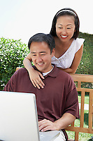 Couple Using Laptop in Garden