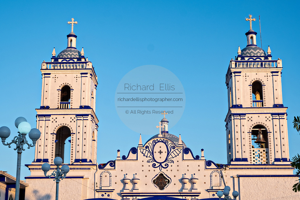 The Basilica of Our Lady of Mount Carmel Catholic Church at sunset in Catemaco, Veracruz, Mexico. The town is built along a tropical freshwater lake at the center of the Sierra de Los Tuxtlas mountains, is a popular tourist destination and known for free ranging monkeys, the rainforest backdrop and Mexican witches known as Brujos.