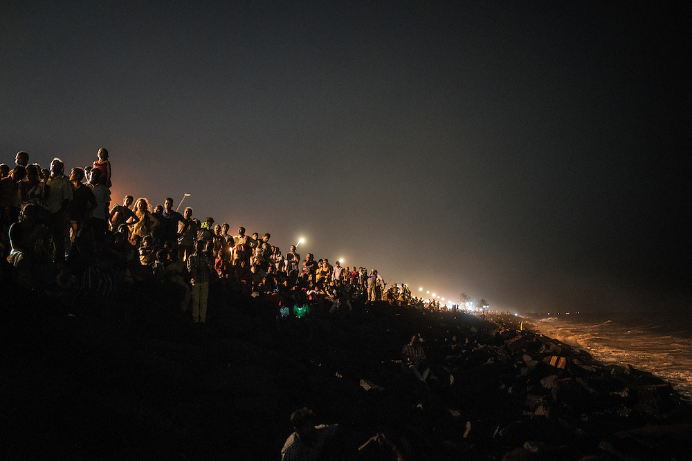 Spectators line the seawall in Pondicherry to watch dozens of Lord Ganesha statues being immersed into the sea for the the Ganesh Chaturthi Festival.  Pondicherry, India.