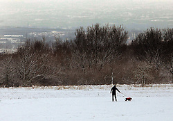 Licensed to London News Pictures. 14/01/2013. Gateshead, UK.  Snow blankets much of the North East with heavier coverage at higher locations - Man walking his dog near the Angel of the North. Photo credit: Adrian Don/LNP
