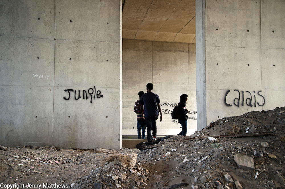 Calais August 2015 The Jungle, camp of migrants, most of whom are trying to get to England. Three young people set off to walk to the Channel Tunnel terminal under the motorway. The words 'jungle' and 'Calais' are written on the concrete;