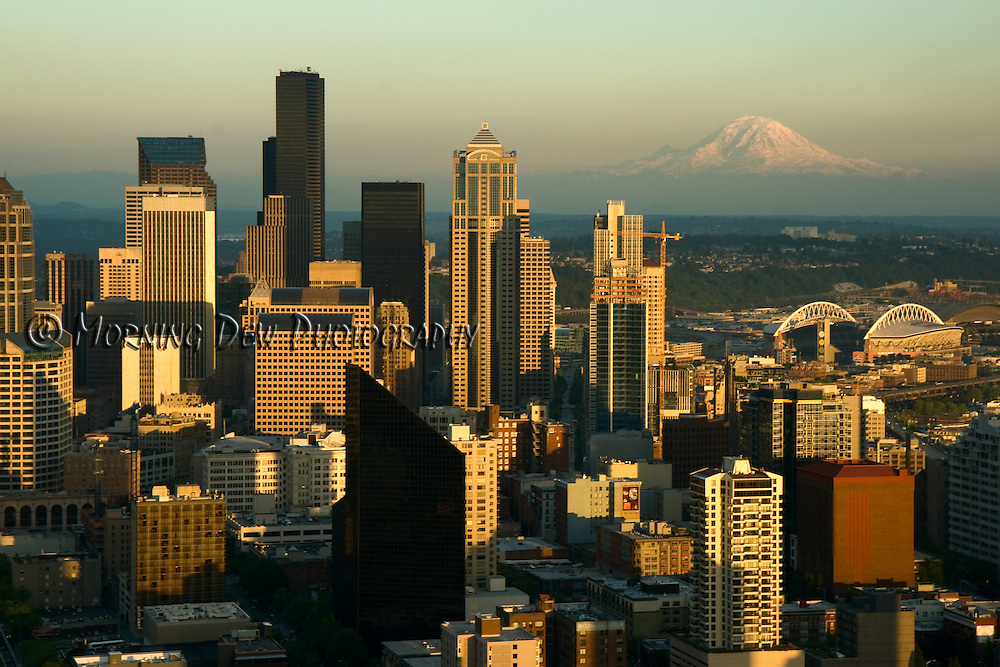The evening sun baths the Seattle skyline in a warm glow and illuminates the distant snow-capped peak of Mount Rainier.