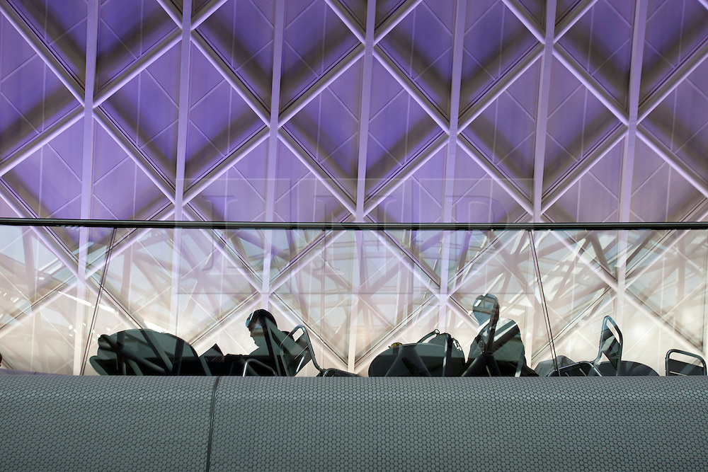 © licensed to London News Pictures. London, UK 19/03/2012. Commuters sit underneath the roof of the new concourse at King's Cross train station in London which opened to commuters today (19/03/2012). Photo credit: Tolga Akmen/LNP