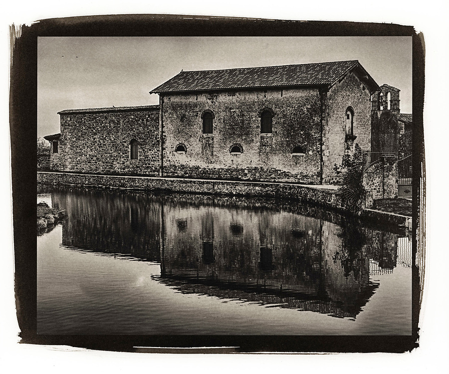 Chateau de Virieu is an old stone chateau with strong reflections from a small pond in the town of Pelussin in France.