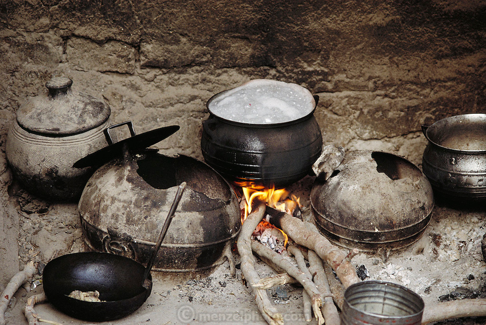 Natomo family dinner of rice porridge cooks on the hearth over a wood fire.  Published in Material World, Meals of the World gallery, page 176. The Natomo family lives in two mud brick houses in the village of Kouakourou, Mali, on the banks of the Niger River. They are grain traders and own a mango orchard. According to tradition Soumana is allowed to take up to four wives; he has two. Wives Pama and Fatoumata are partners in the family and care for their many children together.