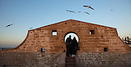 A man and woman share the view through a porthole at the Skala du Port in Essaouira, Morocco. The port hole allows a view to the walled coastal city of Essaouira.