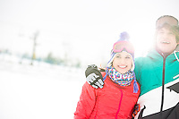 Cheerful young couple standing arm around in snow