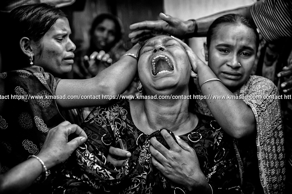 Relative grieve after identifying the body of a loved one killed in last weeks collapse of the eight-story building Rana-Plaza in Savar, Outside Dhaka on 3 May 2013.