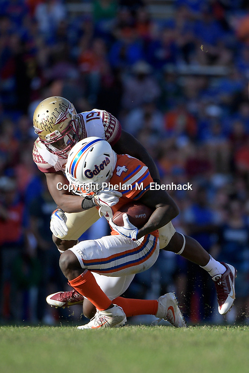 Florida State defensive back A.J. Westbrook (19) tackles Florida wide receiver Brandon Powell (4) after catching a pass during the second half of an NCAA college football game Saturday, Nov. 25, 2017, in Gainesville, Fla. FSU won 38-22. (Photo by Phelan M. Ebenhack)