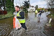 © Licensed to London News Pictures. 09/02/2014. Wraysbury, UK. Volunteers help people through the rising waters. Flooding in Wraysbury in Berkshire today 9th February 2014 after the River Thames burst its banks. Photo credit : Stephen Simpson/LNP