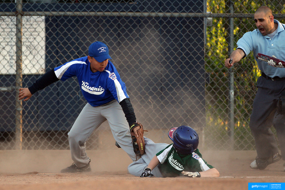 A young pitcher gets the out at home plate after covering a pass ball and receiving from the catcher during the Norwalk Little League baseball competition at Broad River Fields,  Norwalk, Connecticut. USA. Photo Tim Clayton