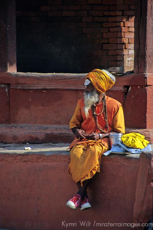 Asia, Nepal, Bhaktapur. A Sadhu in sneakers sits in Durbar Square, Bhaktapur.