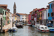 "The tilting campanile (bell tower) of the Church of San Martino rises above houses in Burano, in the Venetian Lagoon, Italy, Europe. Burano, known for knitted lacework, fishing, and colorfully painted houses, is a small archipelago of four islands linked by bridges in the Venetian Lagoon. Burano's traditional house colors are strictly regulated by government. The Romans may have been first to settle Burano. Romantic Venice (Venezia), ""City of Canals,"" stretches across 100+ small islands in the marshy Venetian Lagoon along the Adriatic Sea in northeast Italy, between the mouths of the Po and Piave Rivers. Venice and the Venetian Lagoon are honored on UNESCO's World Heritage List."