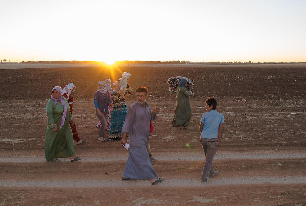 Syrian/Kobane refugees looking back to their village after crossing Yumurtalık border at Turkish side.