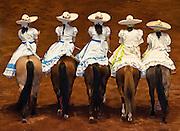 Women horse riders wearing traditional  Escaramuza Charra costume at Lienzo Charro charreada show, Guadalajara, Mexico.
