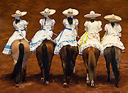 Women horse riders wearing traditional  Escaramuza Charra costume at Lienzo Charro charreada show, Guadalajara, Mexico.