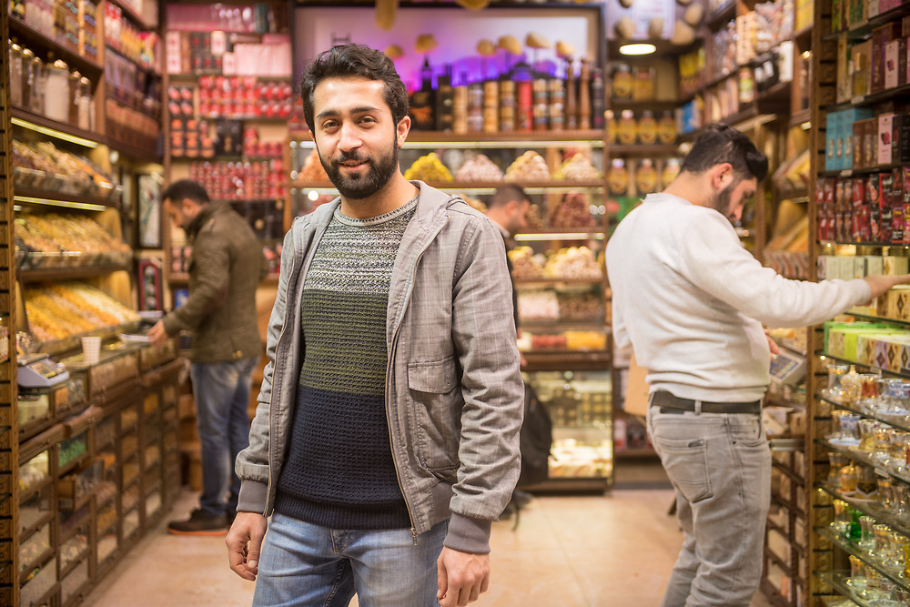 An adult male merchant smiles for photo in front of spice shop in Istanbul Spice bazaar in Turkey