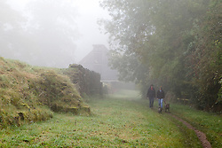 © Licensed to London News Pictures. 21/10/2012. KENILWORTH, UK. Dog walkers are seen in mist as they take a morning autumn walk at Kenilworth Castle in Warwickshire today. Photo credit: Matt Cetti-Roberts/LNP
