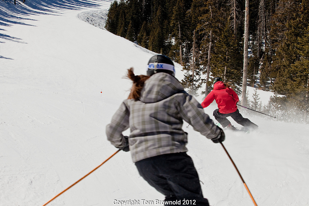 Arizona Snow Bowl woman skiers skiing on a sunny hard packed day
