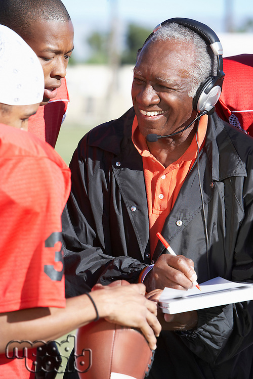Football Coach Talking to Two Players