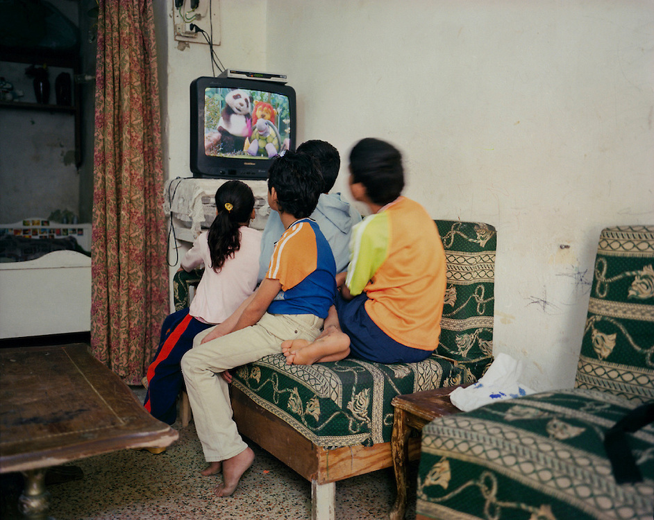 Fatin and Samir Kamil&rsquo;s children, unable to attend school, watch TV. Amman, Jordan<br /><br />&copy;2007-2011 Lori Grinker<br /> All Rights Reserved