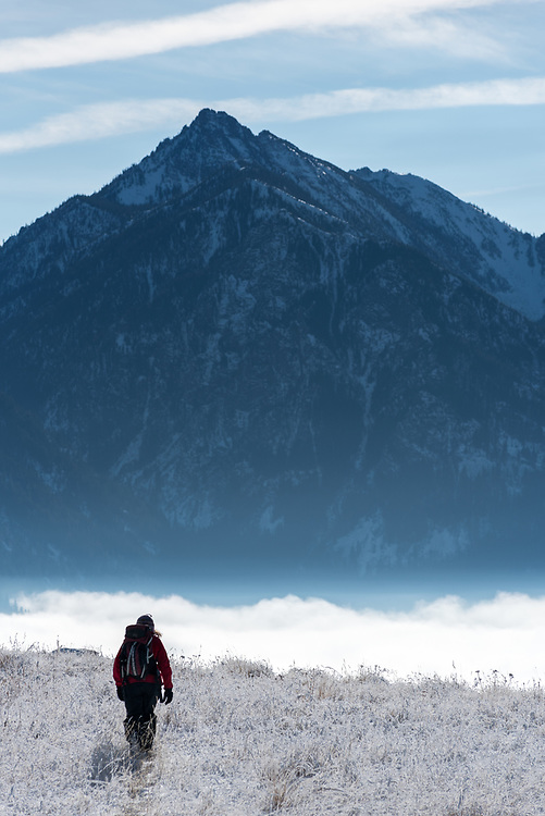 Woman hiking on Wallowa Lake's east moraine with fog filling the Wallowa Lake basin and the Wallowa Mountains in the background, Oregon.