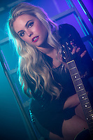 Blonde woman holding electric guitar in a backstage