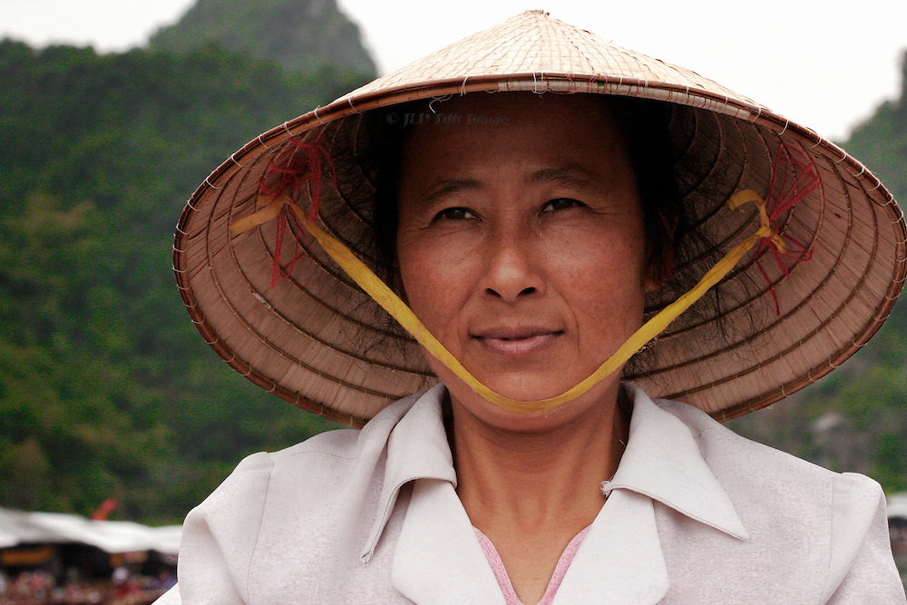 Portrait of a woman boat rower, who takes pilgrims to the Perfume Pagoda.  Head shot, conical straw hat tied under the chin, serious but pleasant facial expression.