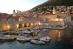 Europe, Croatia, Dalmatia, Dubrovnik.  Marina, old city walls, and Dominican Monastery at dusk.The historic center of Dubrovnik is a UNESCO World Heritage site.