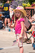 Girl waving to the people in the Fourth of July parade in Iowa